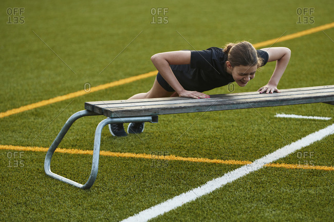Teenage girl doing push-ups on bench in playing field