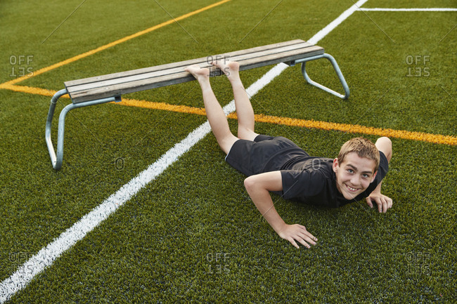 Teenage boy doing push-ups on bench in playing field