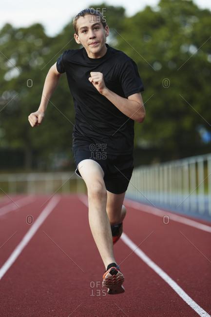 Teenage boy running in sports track