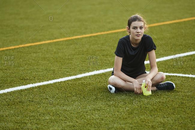 Teenage girl sitting on playing field