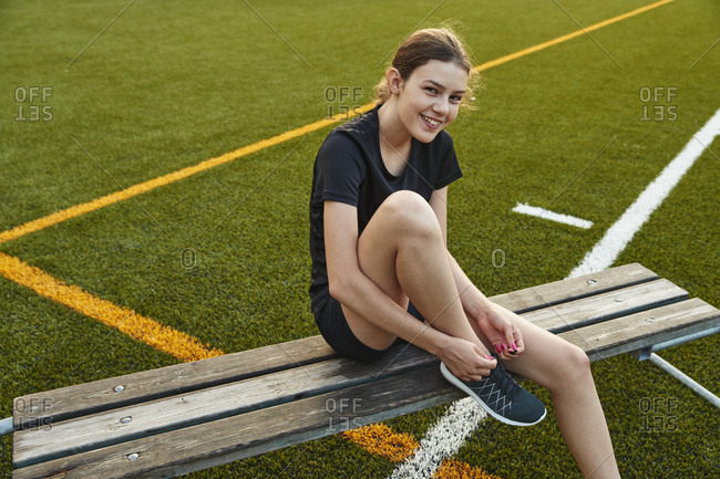 Smiling teenage girl tying shoelace while sitting on bench in playing field