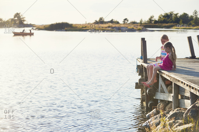 Girls sitting on pier by lake