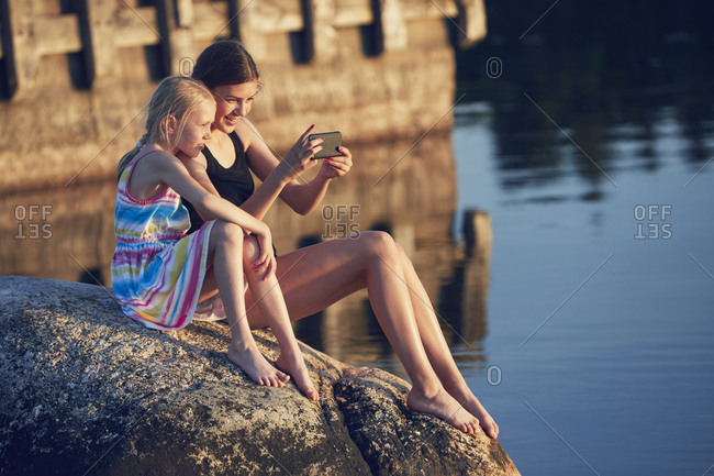 Girls using cell phone by lake