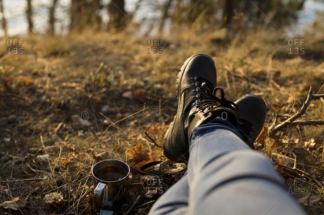 Person relaxing with coffee, low section