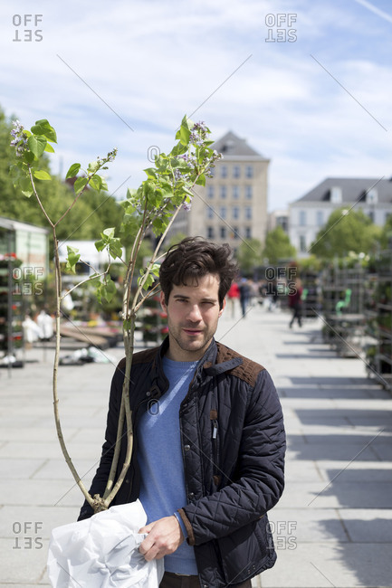 Man at outdoor market with a tree