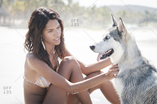 Mexico- Riviera Nayarit beach- young woman sitting with husky dog