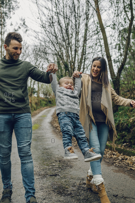 Pregnant woman having fun with family in forest in autumn