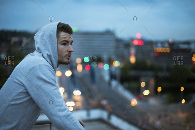 Athlete wearing hoodie above the city at dawn