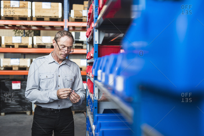 Man in storehouse examining screw