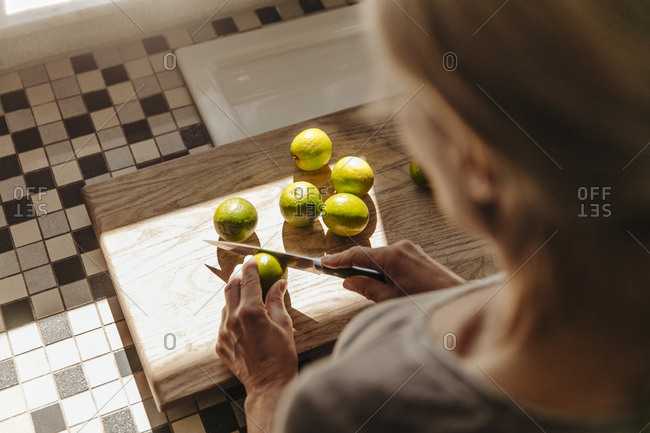 Woman in kitchen cutting limes