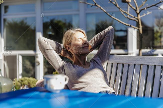 Woman relaxing on garden bench