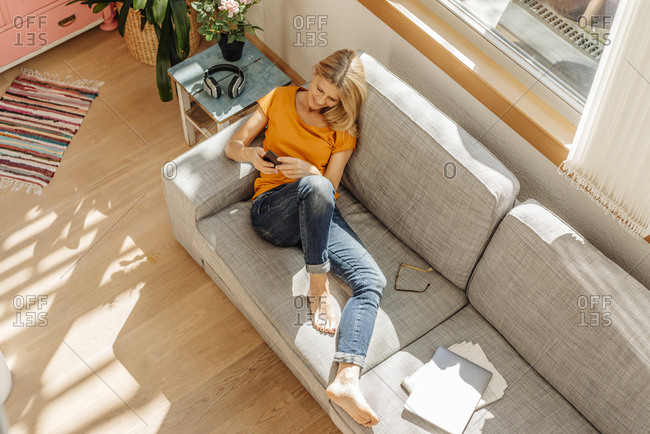 Woman at home on couch with cell phone