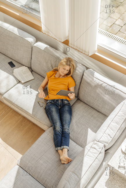 Woman at home on couch with tablet