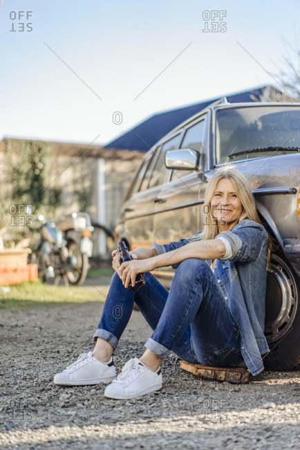Woman sitting at car drinking a beer