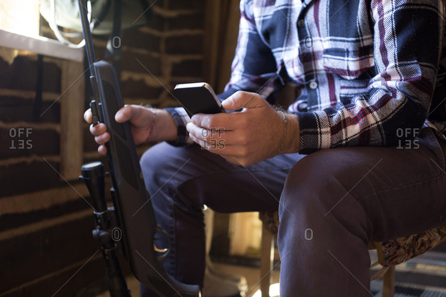 Man sitting down with rifle and cell phone
