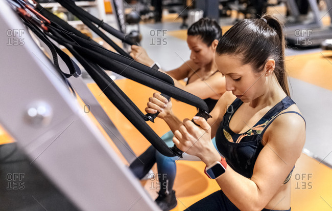 Two women doing suspension training in the gym