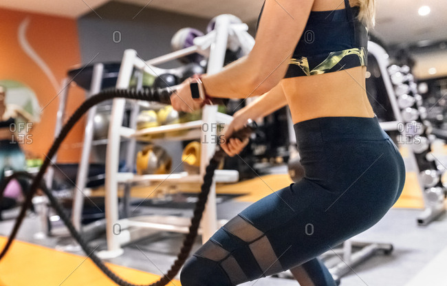 Young woman doing battle rope exercise at gym