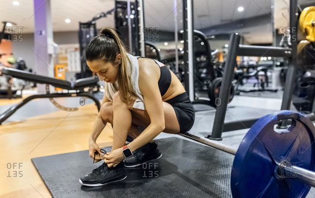 Young woman tying her shoes in gym