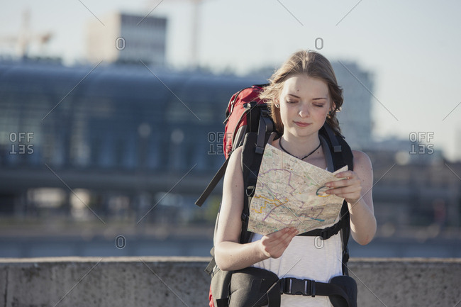 Germany- Berlin- Young woman with backpack looking at map