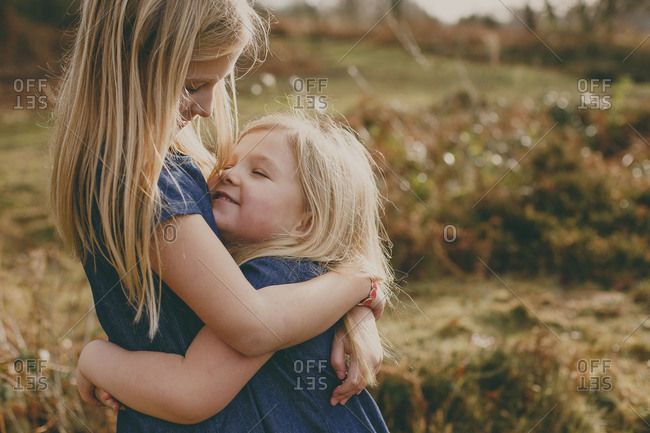 Two cute blond sisters cuddling outdoors