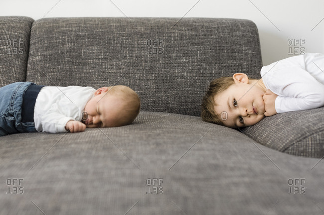 Sleeping newborn baby boy and his brother on couch