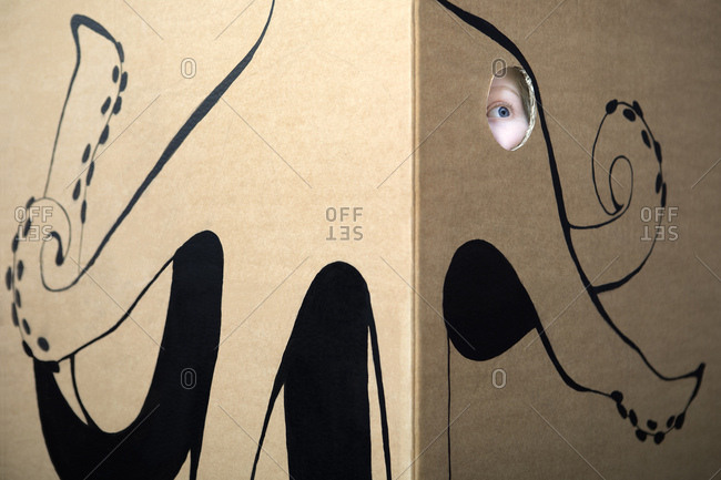 Girl peeking out of cardboard box painted with an octopus