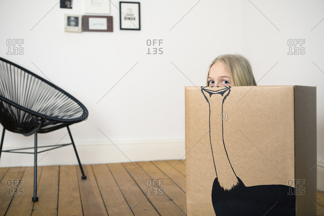 Girl inside a cardboard box painted with an ostrich
