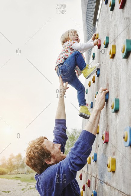 Girl climbing on a wall supported by father