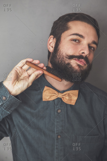 Man combing his beard with a wooden brush- wearing denim shirt and cork bow tie
