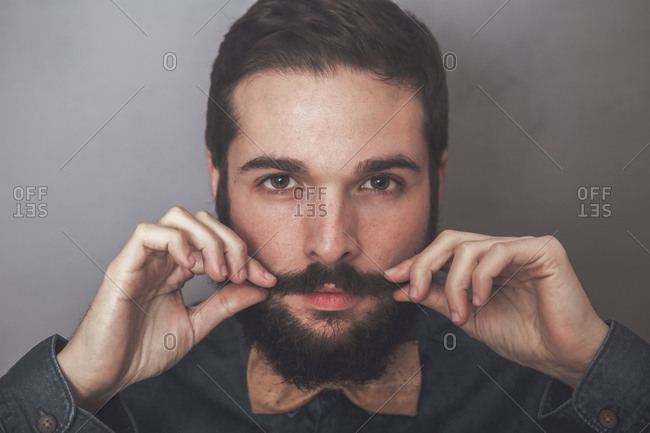 Bearded man adjusting his mustaches- wearing denim shirt and cork bow tie
