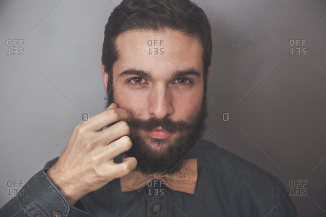 Bearded man adjusting his moustache- wearing denim shirt and cork bow tie