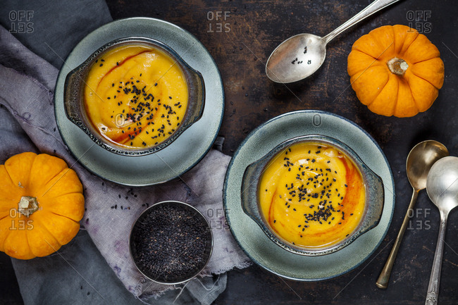 Bowls of creamed pumpkin soup sprinkled with black cumin next to pumpkins