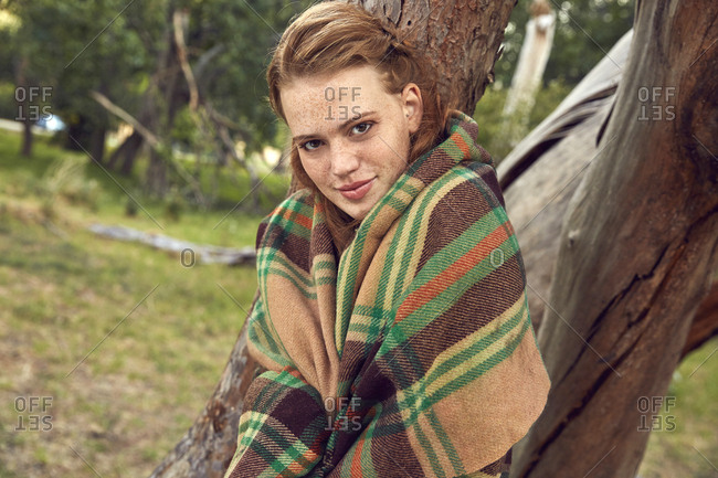 Portrait of young woman in nature wrapped in blanket