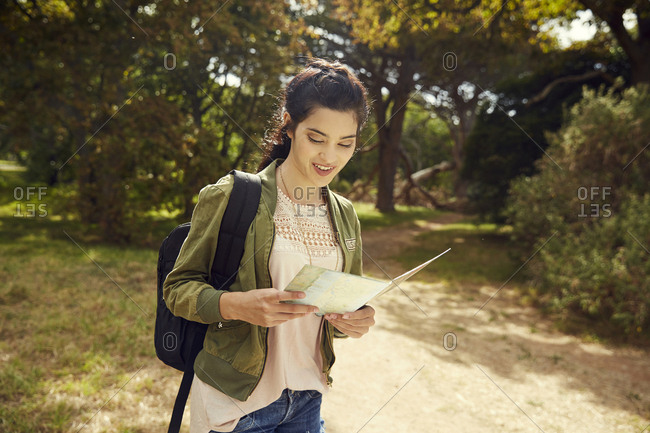 Young woman with map orientating in nature
