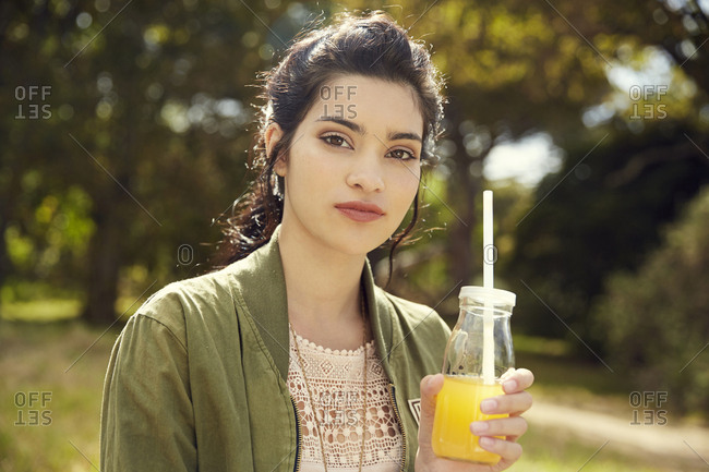 Portrait of young woman with glass of juice