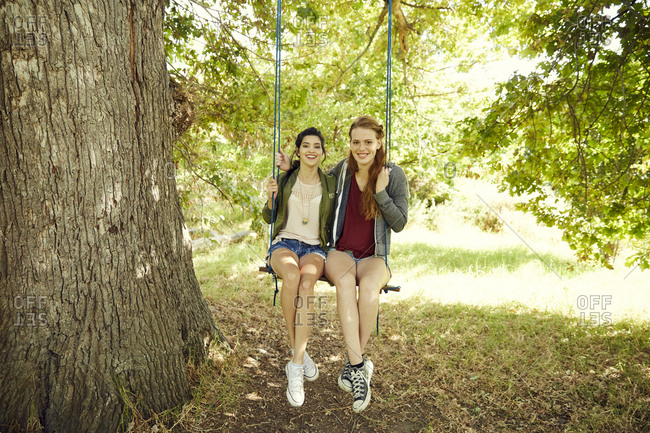 Two best friends sitting together on a swing