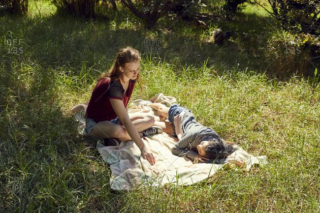 Two friends relaxing on blanket on a meadow