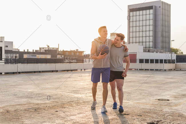 Friends playing basketball at sunset on a rooftop