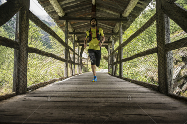 Italy- Alagna- man running on wooden bridge in the mountains