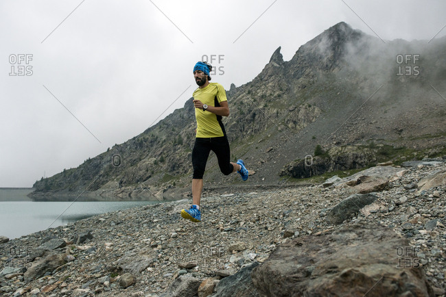 Italy- Alagna- trail runner on the move at a lake near Monte Rosa mountain massif