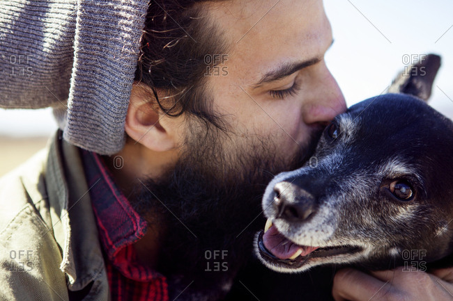 Close-up of affectionate man kissing dog during sunny day