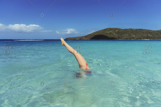 Low section of woman diving in sea against blue sky