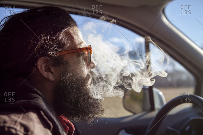 Side view of hipster smoking in car during vacation