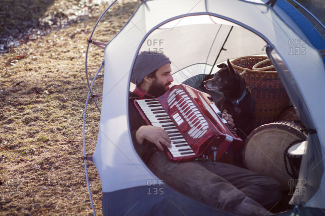 Man playing accordion for dog while sitting in tent at campsite