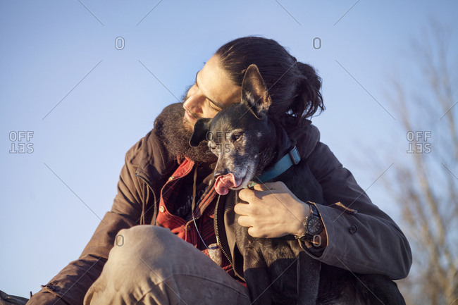 Affectionate man embracing dog while sitting against clear blue sky