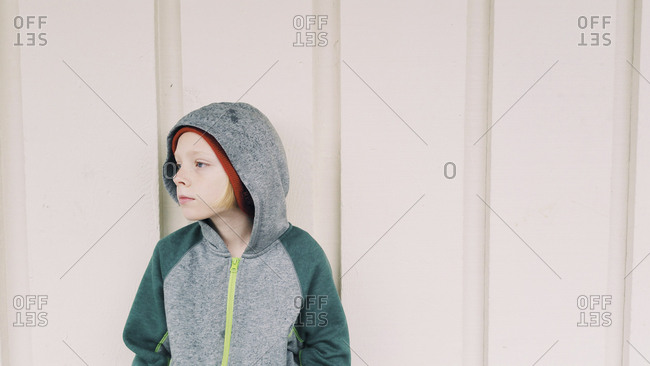 Thoughtful boy in hooded shirt looking away while standing against wall