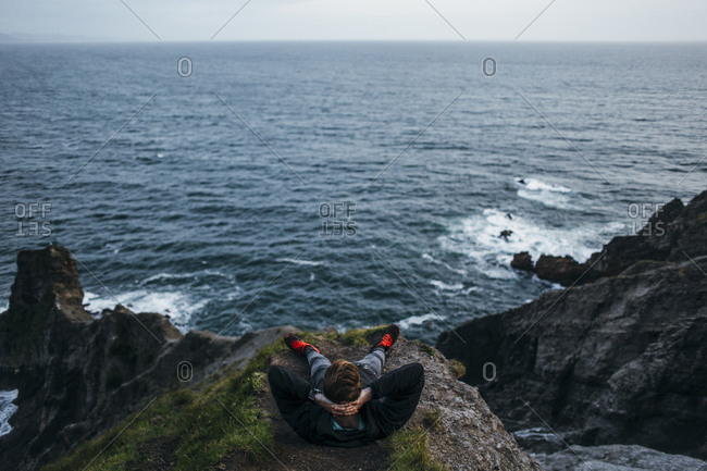High angle view of hiker sitting with hands behind head on cliff against seascape