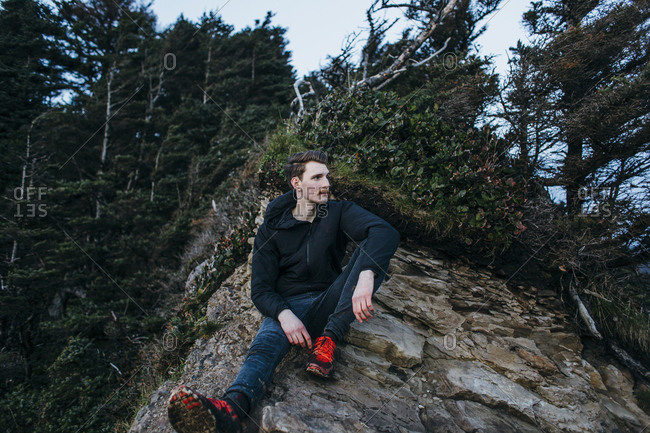 Thoughtful male hiker sitting on rock against trees
