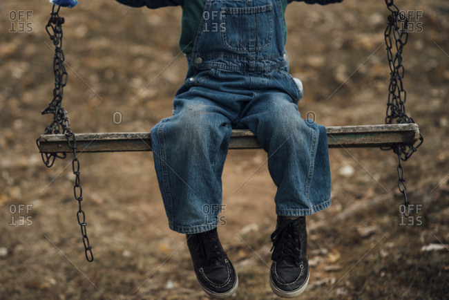 Low section of boy sitting on swing
