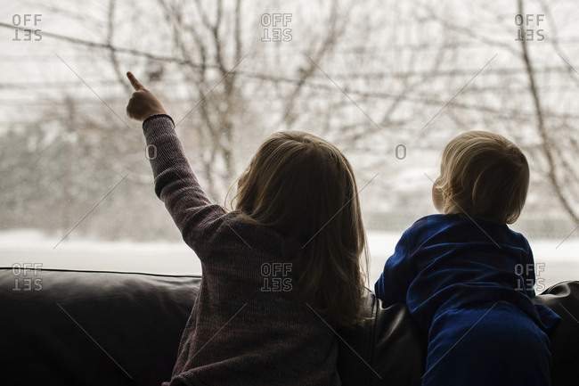 Rear view of siblings looking through window while relaxing on sofa at home during winter
